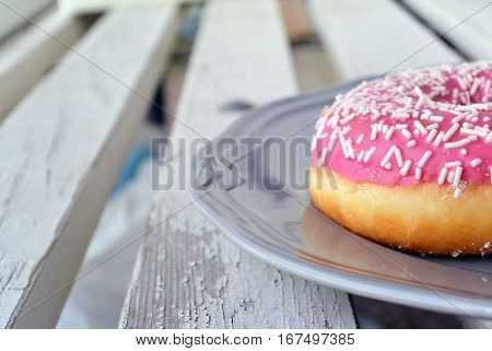 Light background with detail of sweet pink icing donut with sprinkles on gray plate. Selective focus