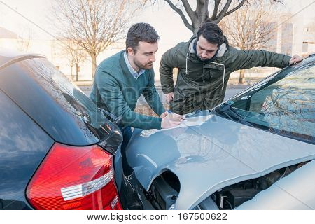 Two Men Writing A Car Insurance Claim After A Car Crash