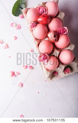 Pink Easter eggs on light background. Copyspace. Still life photo of lots of pink easter eggs.Background with easter eggs. Pink eggs and roses. Easter photo concept