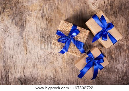 Gift boxes from recycled paper decorated with blue satin bow on the old wooden background. Copy space