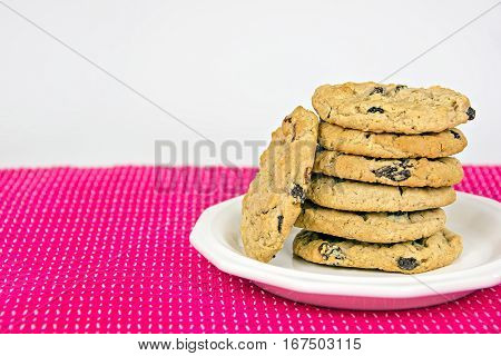 oatmeal cookies with raisins stacked on white plate and bold pink tablecloth