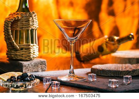 Martini in the glass, icecubes, serving boards over fireplace background