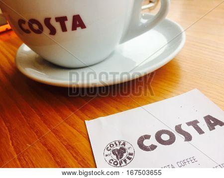 CREWE, UK - JANUARY 30, 2016: A Costa coffee till receipt with coffee cup and saucer on a wooden table, Crewe, Cheshire, UK