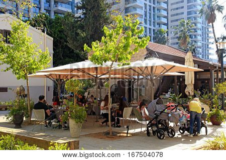 TEL AVIV, ISRAEL - APRIL 7, 2016: People rest in outdoor cafe in the modern open air commercial center and park Sarona, Tel Aviv, Israel