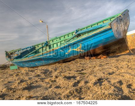 Blue fishing boat on the bank of ocean in Paracas.