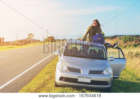 Happy woman sitting on car roof. Car parking side road.