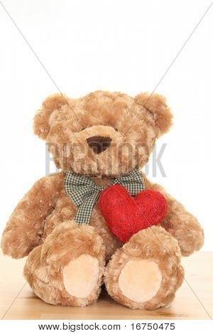 close-ups of cute teddy bear with big heart isolated on white