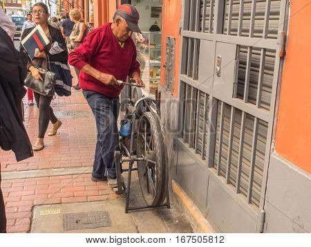 Lima Peru - May 27 2016: Man is sharpening the knife on the street of Lima