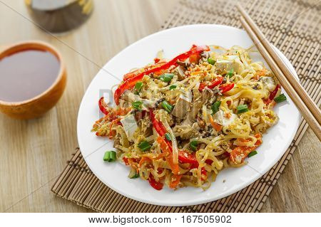 Asian food. Fried rice noodles with tofu vegetables and shiitake mushroom. Oriental cuisine meal. Close-up.