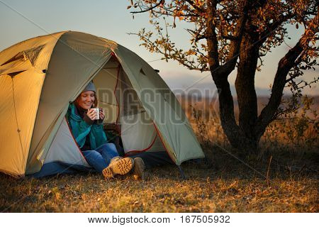 Young beautiful woman in colorful sports wear and trekking shoes sitting in light olive bivouac and drinking from metal mug at autumn landscape background with sunset sunlight