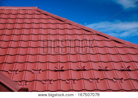 New red sheet metal tile roof cover with blue sky in the background