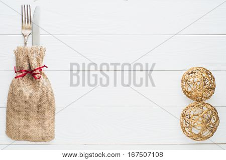 Rustic cutlery set: vintage knife and fork on a white wooden background. Table with antique cutlery on the burlap with copy space top view flat lay. Table with cutlery wrapped in burlap.