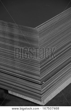 Aluminum sheet metal plates cut to length and stacked on a palette. Black and white