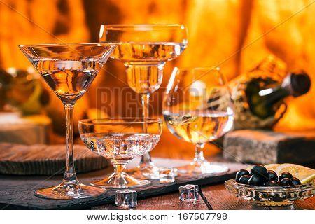 Various shape glasses. on bar counter. Wine bottles in the fire light