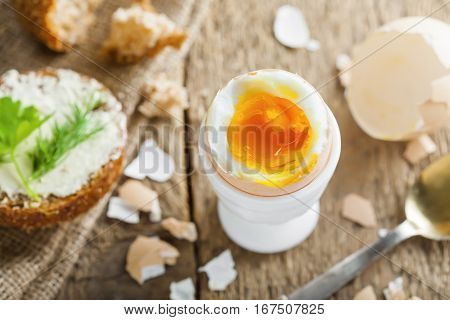 Traditional breakfast with perfect soft boiled egg and sandwich with butter and dill. International cuisine food. Top view.