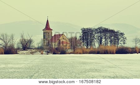 Beautiful old church of St. Linhart. Catholic temple village of Musov - Pasohlavky Czech Republic. Photo of landscape with sunset on a dam New Mills (Nove Mlyny)
