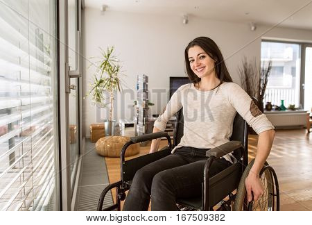 Beautiful young disabled woman in wheelchair at the window at home in her living room