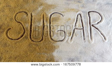 Sugar inscription on white and brown sugary grain, top view