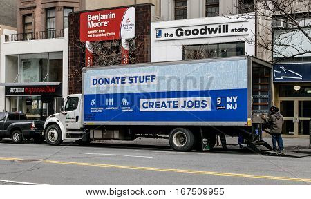 New York January 21 2017: Two employees are unloading a Goodwill truck is parked in front of their store.