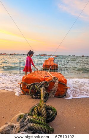 Asian girl walking in the sea and has are floating tank orange color Lrge rope bring a look to the key visual The time in twilight at Pattaya beach of Thailand Asia.