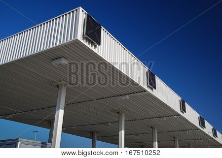 Pay toll with X sign lit covered in white corrugated sheet metal profiles