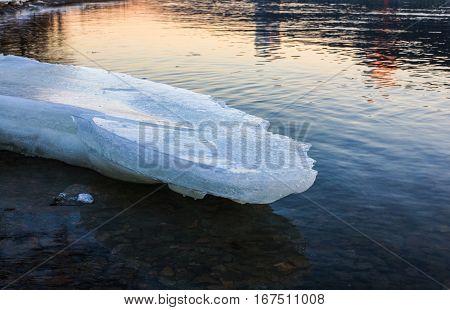 Ice floe melting on the coast at sunset