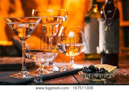 Various glasses with clear liquid. Fire on the background