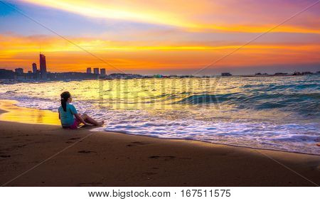 Asian girl relax sitting on the sand of beach nice shot in sunset time at Pattaya Thailand Little blur concept soft feeling.