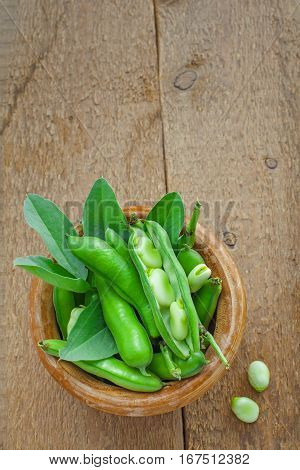 Fresh green broad beans in a bowl. Fresh raw vegetables on a wooden table. Ingredients healthy vegetarian food. Top view.