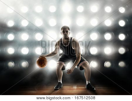 basketball player on floodlight background on parquet with ball