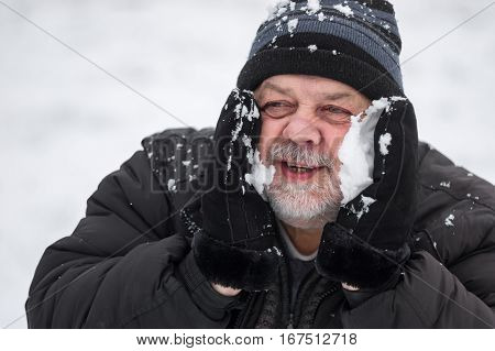 Portrait of senior man warming up his cheeks rubbing them with snow