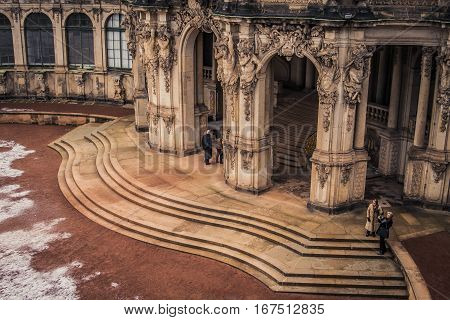 Dresden, Germany - 2 Jan. 2008: View of the courtyard at the Zwinger with tourists admiring the architecture and a fresh layer of snow on the ground