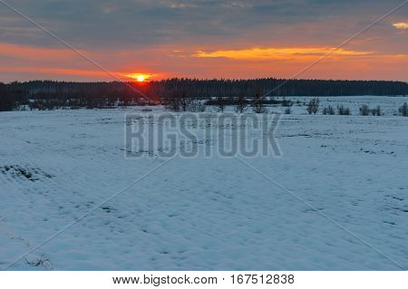 Sunset over agricultural field at winter season in Sumskaya oblast Ukraine