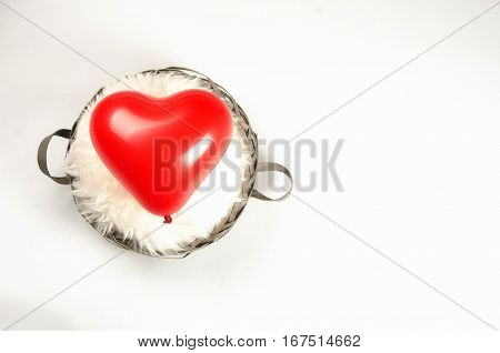Red balloon heart in a basket with lambskin, placed left, on white background