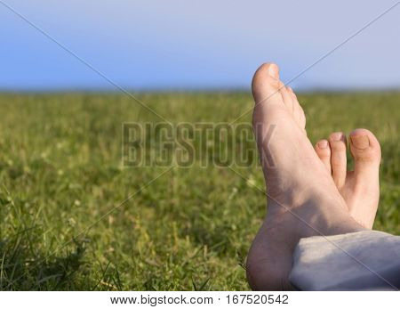 bare feet resting on grass in summer men sunny day in spring