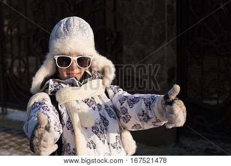 Funny little girl in sunglasses in winter a sunny day. Thumb up sign. Caucasian stylish little girl in winter clothes walking outdoor. Pretty charming little girl. Portrait of little fashion kid girl