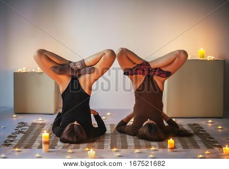 Two young women doing yoga asana lotus in shoulder stand pose on plaid in cozy room with candles. Urdhva padmasana sarvangasane