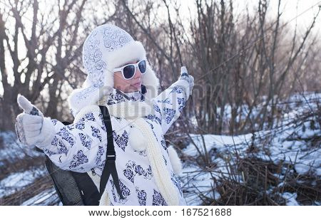 Funny little girl in sunglasses in winter a sunny day. Thumb up sign. Caucasian stylish little girl in winter clothes walking outdoor. Pretty charming little girl. Portrait of little fashion kid girl .