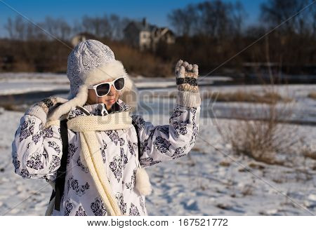 Fashionable beautiful little girl walking by the river on a sunny winter day. Portrait of a stylish little girl on the walking with winter clothes and sunglasses. Caucasian stylish little girl in winter clothes walking outdoor.