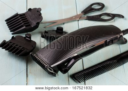 hair trimmer with a comb and scissors on the wooden background