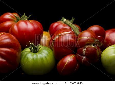 Heirloom tomatoes are captured in a low key image on a black background.