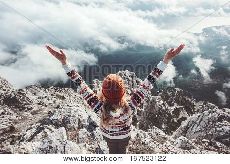 Happy woman traveler on mountain summit hands raised up Travel Lifestyle success concept adventure active vacations outdoor over clouds harmony with nature