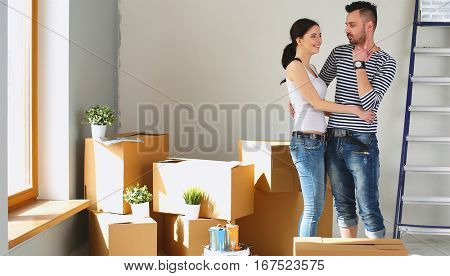 Happy young couple unpacking or packing boxes and moving into a new home