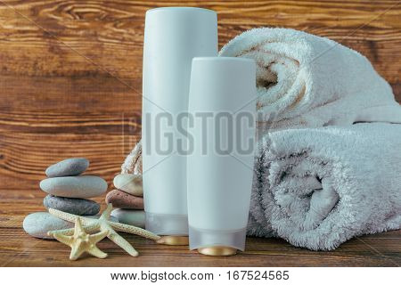spa kit: towels, shampoo bottles on wooden background