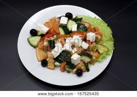 Greek salad on a white plate on a black background. Can be used as a photo for restaurant menus, bistro. European, Mediterranean cuisine.