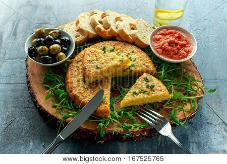 Spanish classic tortilla with potatoes, olives, tomatoes, roccula, bread and herbs