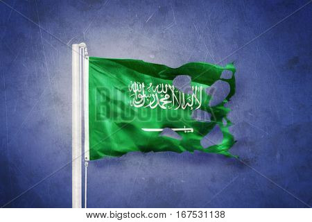 Torn flag of Saudi Arabia flying against grunge background.