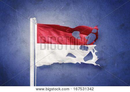 Torn flag of Monaco flying against grunge background.
