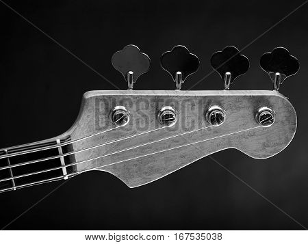 Black and white photo of a bass guitar headstock over dark background.