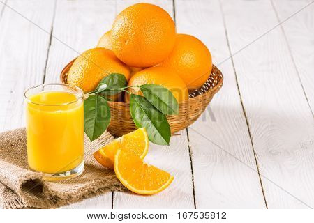 Glass Of Juice And Oranges In A Basket On Table